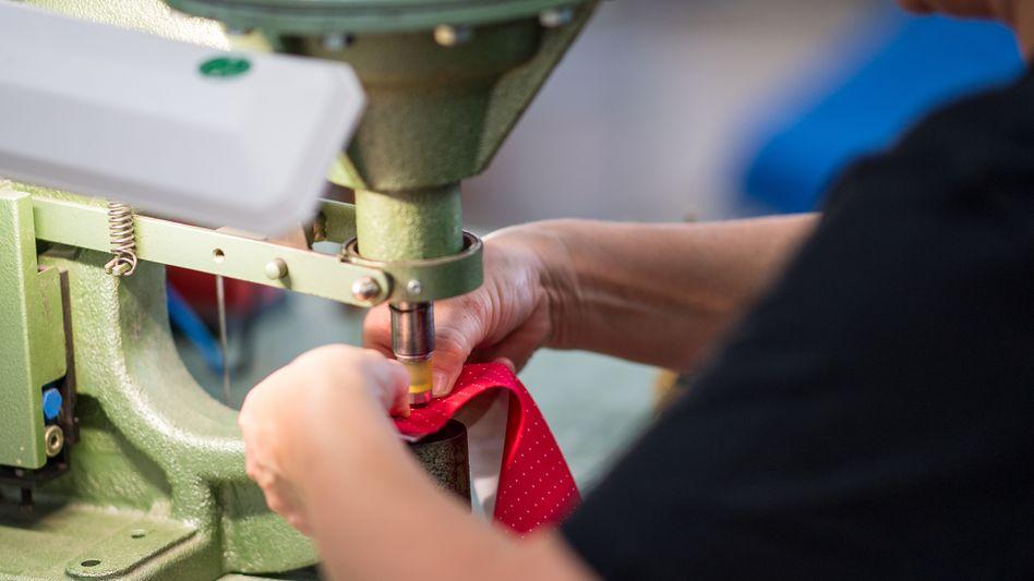 Eine Schneiderin bedient eine Maschine (Symbolbild)