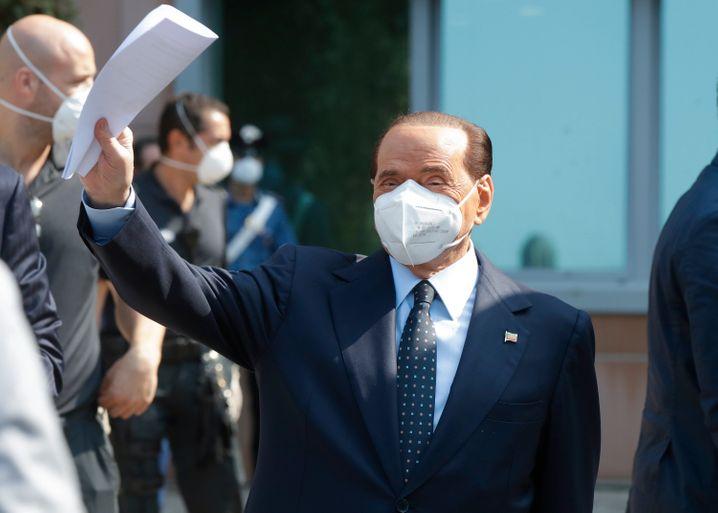 Silvio Berlusconi trug beim Verlassen des Krankenhauses Anzug, Krawatte und Mund-Nasen-Schutz, winkte seinen Anhängern zu und gab eine kurze Erklärung ab