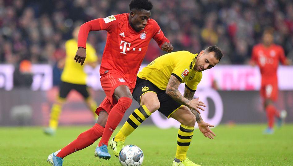 Bayern Münchens Alphonso Davies zieht im Spitzenspiel gegen Borussia Dortmund an Paco Alcácer vorbei. Davies erzielte am 11. Spieltag die Bestnote.