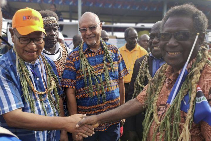 John Momis (l.), Präsident der Autonomen Region Bougainville, schüttelt dem Abgeordneten William Nakin die Hand