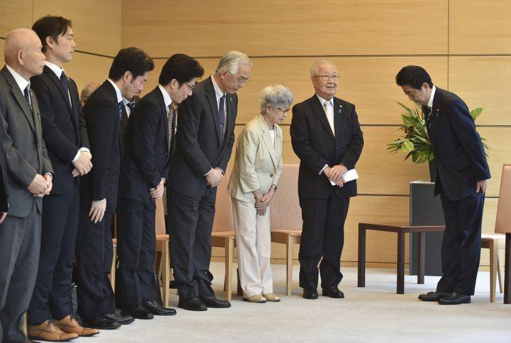 Abe (r.) bei einem Treffen mit Angehörigen von nach Nordkorea verschleppten Japanern