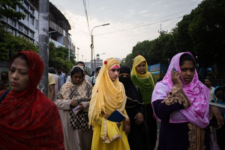 Textile workers walk to their factories on the last working day before Eid.