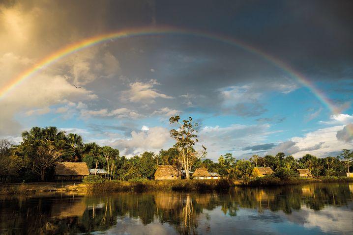 Leben am Fluss: Ein Regenbogen erhebt sich über diesem Uferdorf