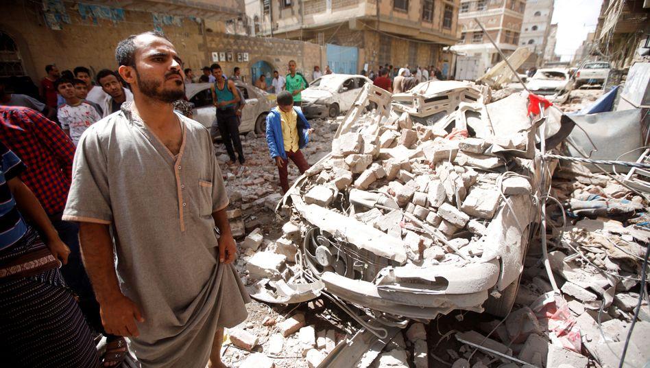 Menschen vor einem von Bomben zertrümmerten Auto in Sanaa