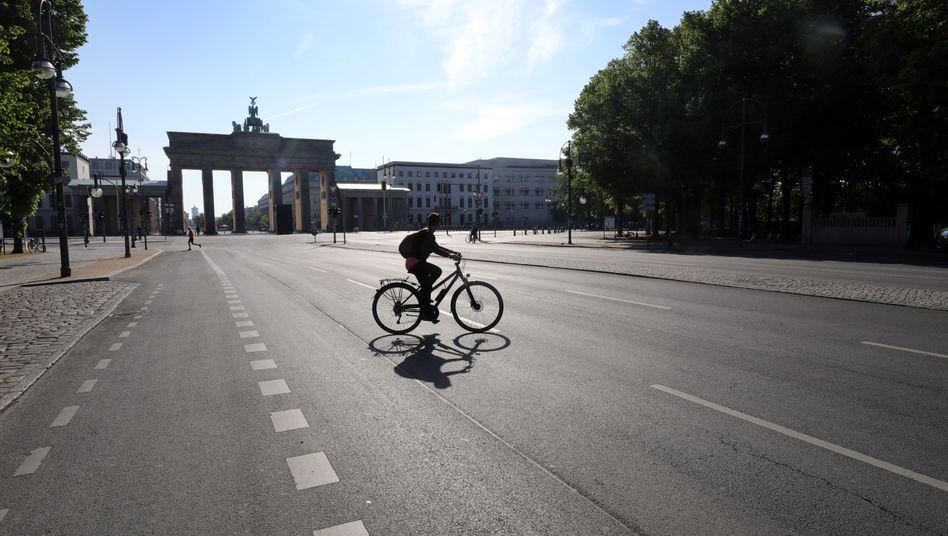 Radfahrerin und Jogger im Mai auf der sonst verkehrsreichen Straße des 17. Juni in Berlin