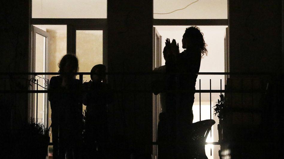 Bewohner eines Hauses in Köln stehen auf ihrem Balkon und klatschen