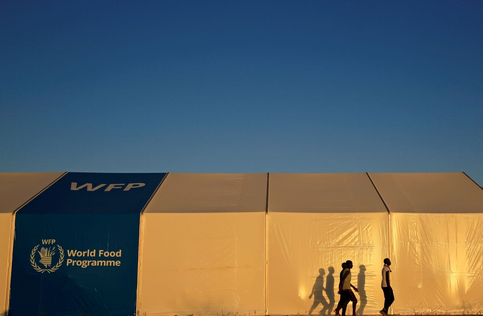 Ethiopian refugees fleeing from the ongoing fighting in Tigray region, walk past a World Food Programme tent, at the Um-Rakoba camp, on the Sudan-Ethiopia border, in the Al-Qadarif state