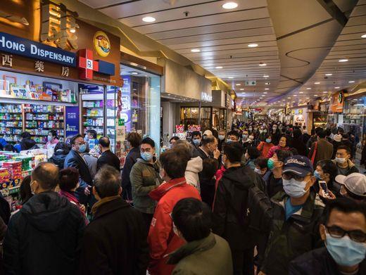 Menschen in Hongkong warten vor einer Apotheke, um sie Atemschutzmasken zu besorgen
