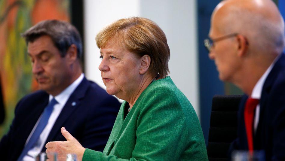 Kanzlerin Angela Merkel mit Bayerns Ministerpräsident Markus Söder (l.) und Hamburgs Erstem Bürgermeister Peter Tschentscher