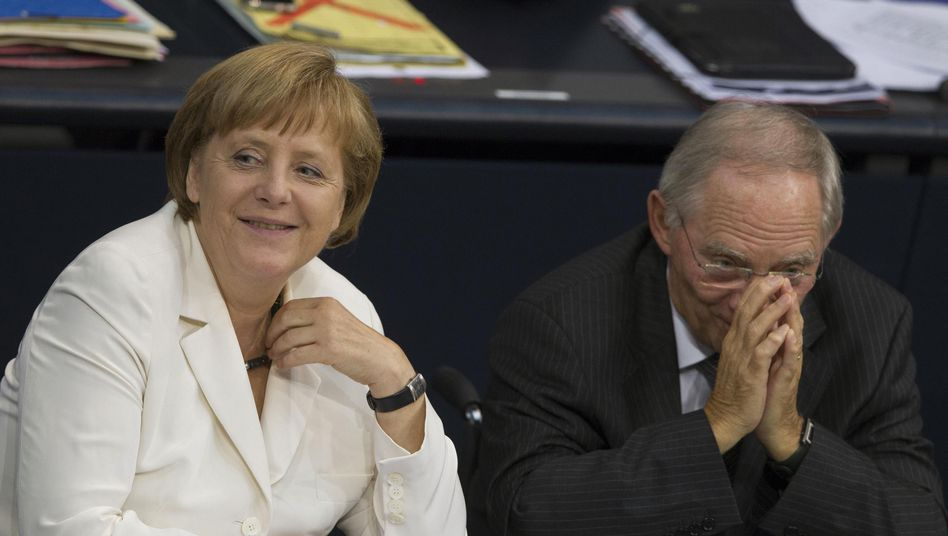 German Chancellor Angela Merkel and her finance minister, Wolfgang Schäuble, talk during Friday's crucial parliamentary debate.