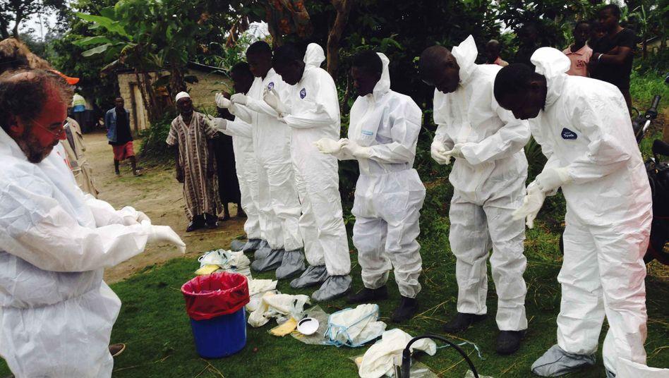 Schutz vor einer Ansteckung: Freiwillige bereiten sich in Sierra Leone darauf vor, Opfer der Epidemie zu bergen