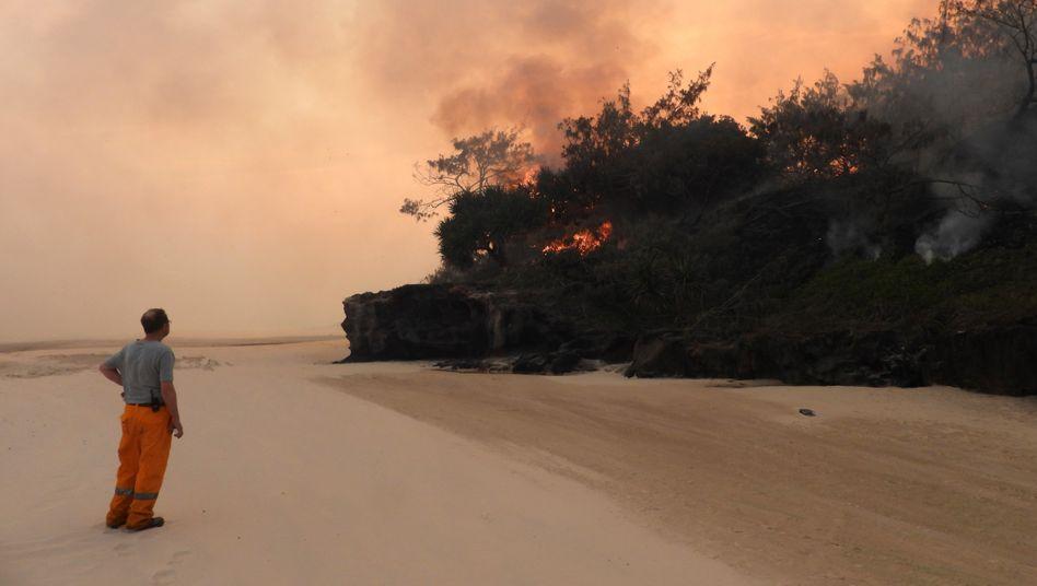 Ein Feuerwehrmann steht an einem Strand von Fraser Island und beobachtet einen Brand