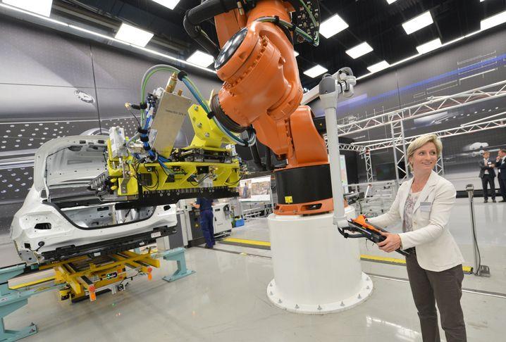 """Per Roboterarm setzt Nicole Hoffmeister-Kraut eine Plug-In-Batterie in einen Daimler: """"Verunsicherung in unseren Kernbranchen Maschinen- und Anlagenbau sowie der Automobilwirtschaft"""""""