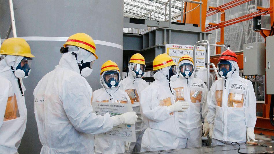 """Japans Premierminister Shinzo Abe (rechts) bei der Besichtigung des Systems """"Alps"""", das verseuchtes Wasser reinigt"""