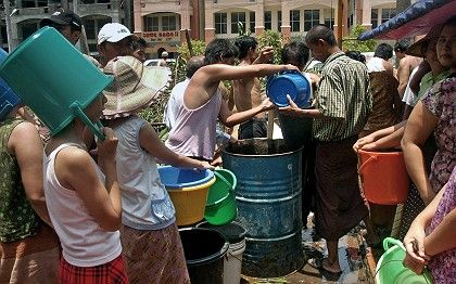 Rangoon residents queue to get drinking water.