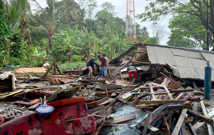 Bewohner durchsuchen nahe des Strandes von Anyer auf Java die Trümmer