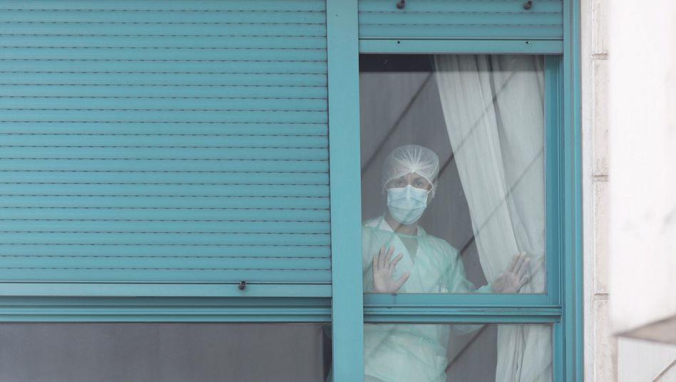 Wann wird es endlich besser? Eine Frau schaut aus dem Fenster eines Pflegeheims in Madrid.