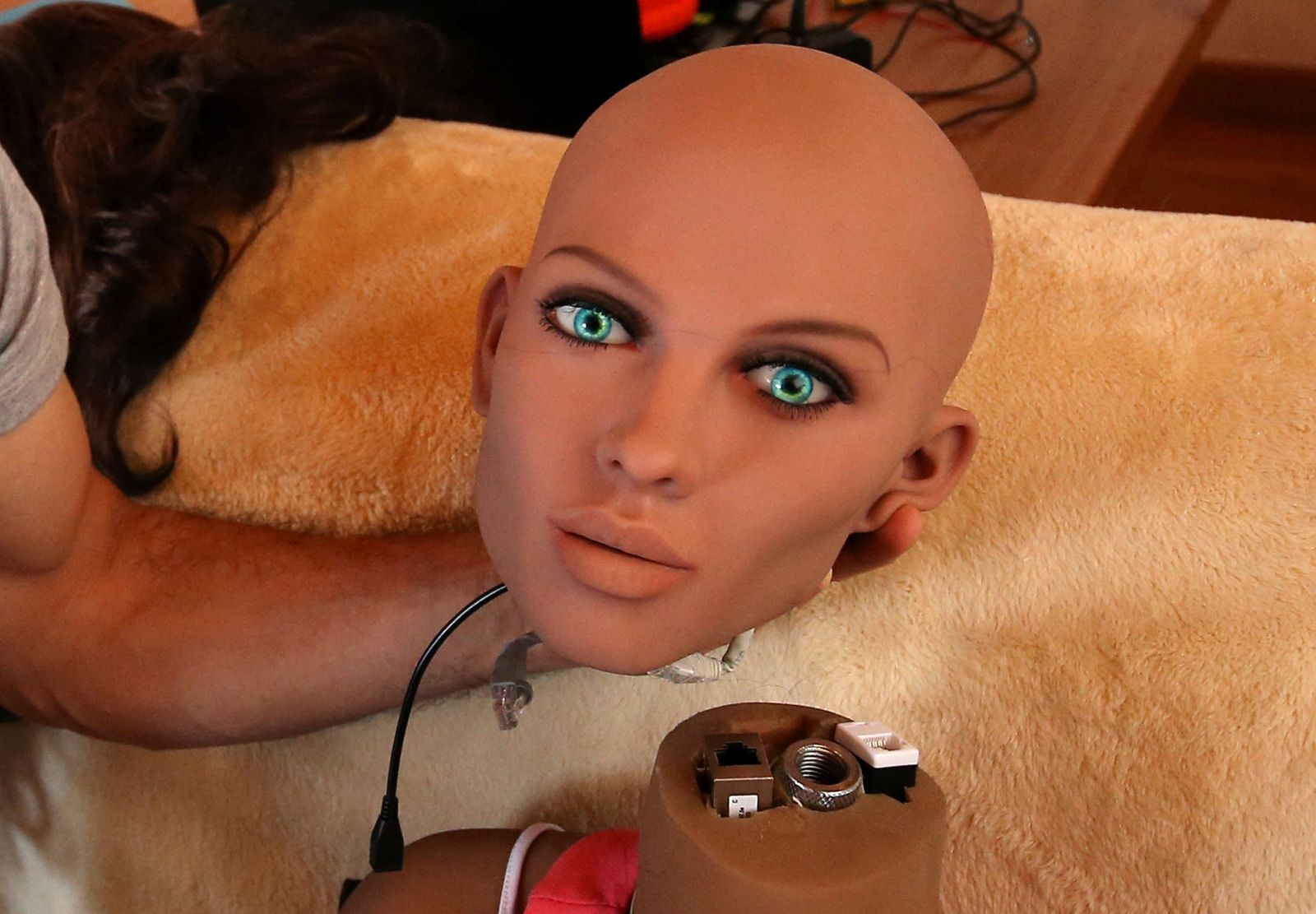 Catalan nanotechnology engineer Sergi Santos holds the head of Samantha, a sex doll packed with artificial intelligence providing her the capability to respond to different scenarios and verbal stimulus, in his house in Rubi, north of Barcelona