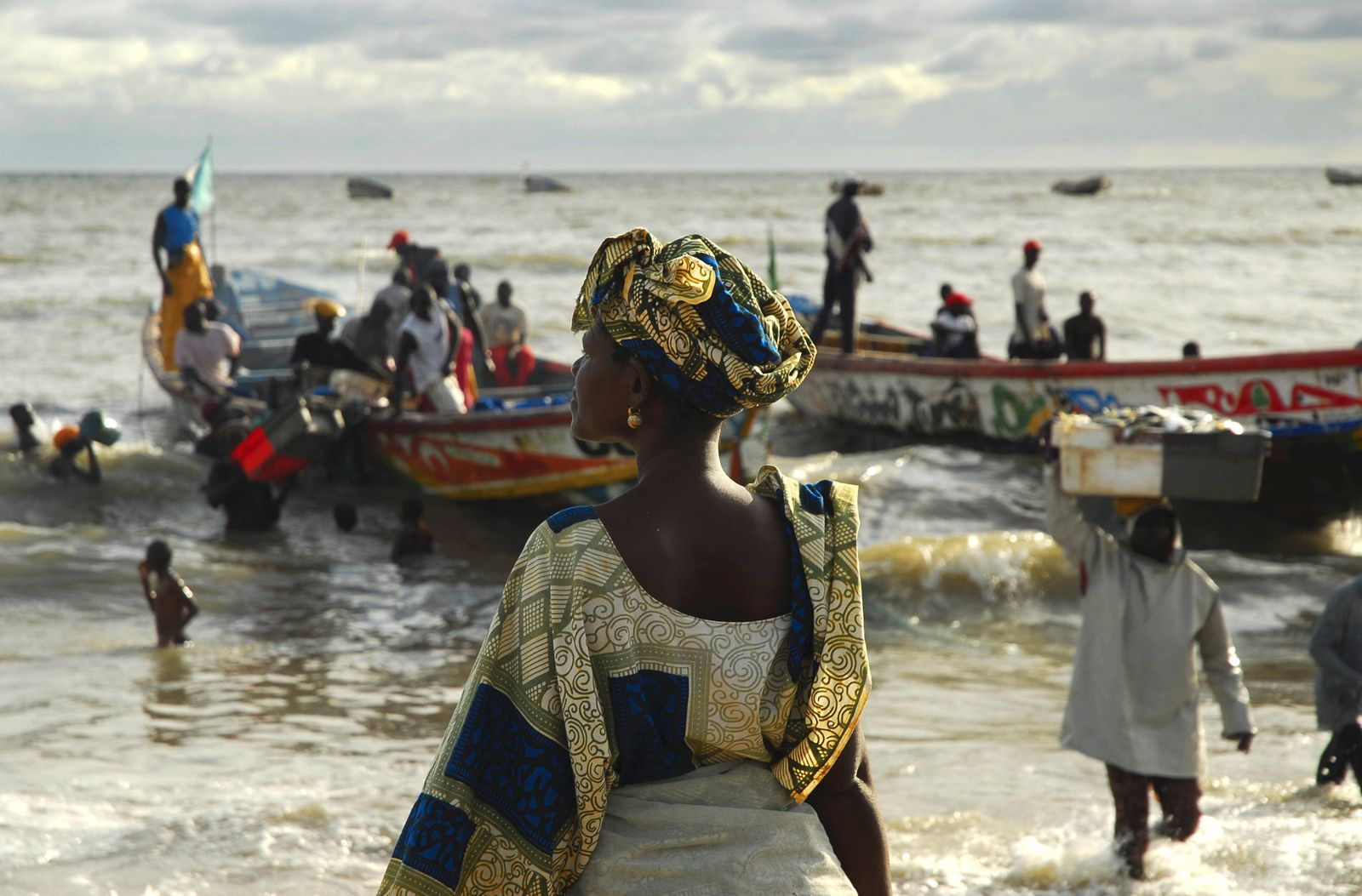 Woman looking out to sea as fishermen arrive on the beach in Mbour in the Petite Cote south of Da