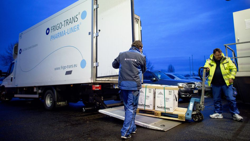 Vaccines are finally arriving en masse in Germany: The driver of a refrigerator truck unloads cases of doses from BioNTech/Pfizer at a logistics center.