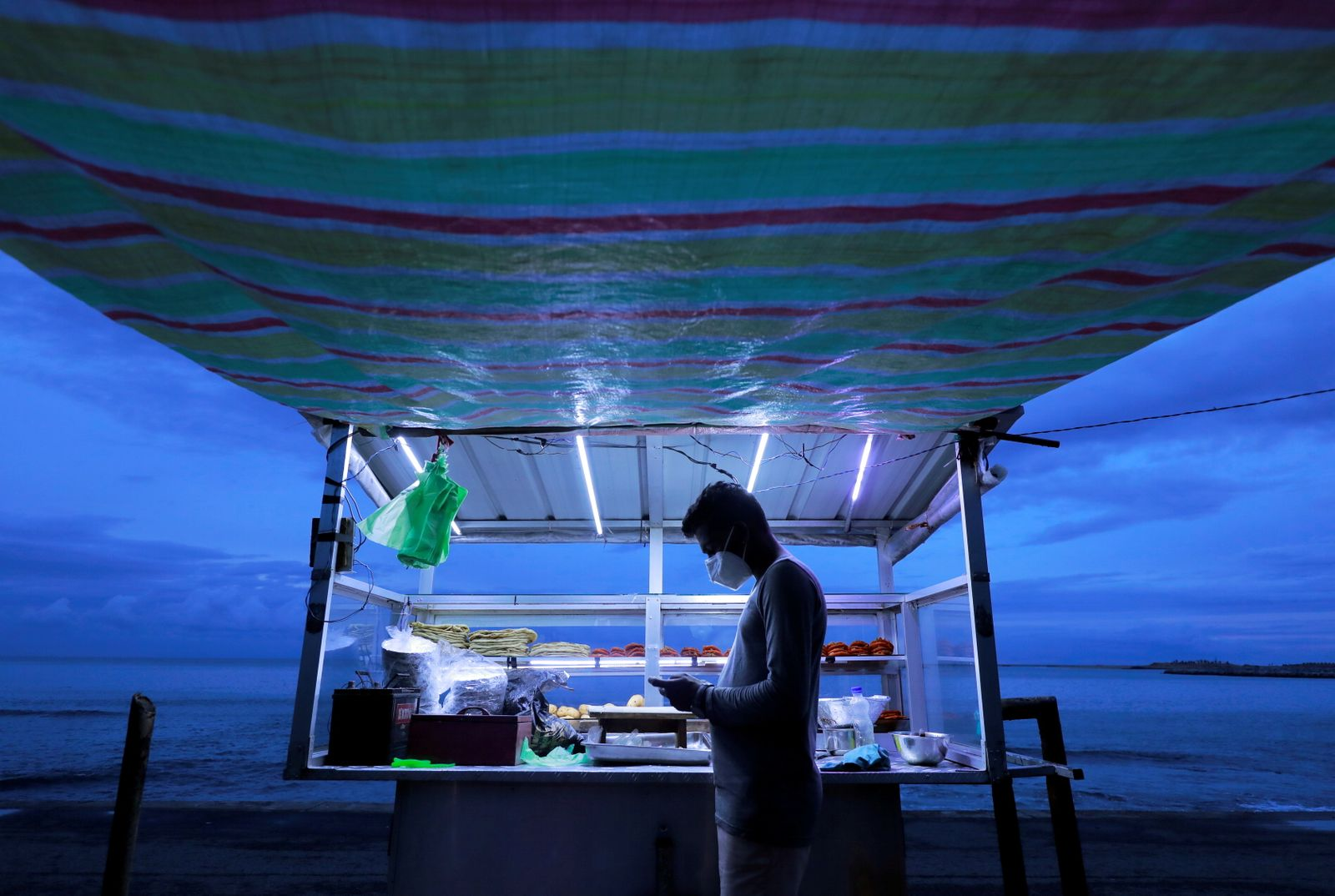 A street vendor wearing a face mask uses his mobile phone while waiting for customers at his food stall near a beach in Colombo