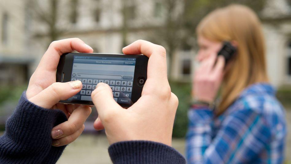 """""""Zahlreiche Einträge in beleidigender, diffamierender und rufschädigender Art"""": Schüler mit Handy auf dem Schulhof (Archivbild)"""