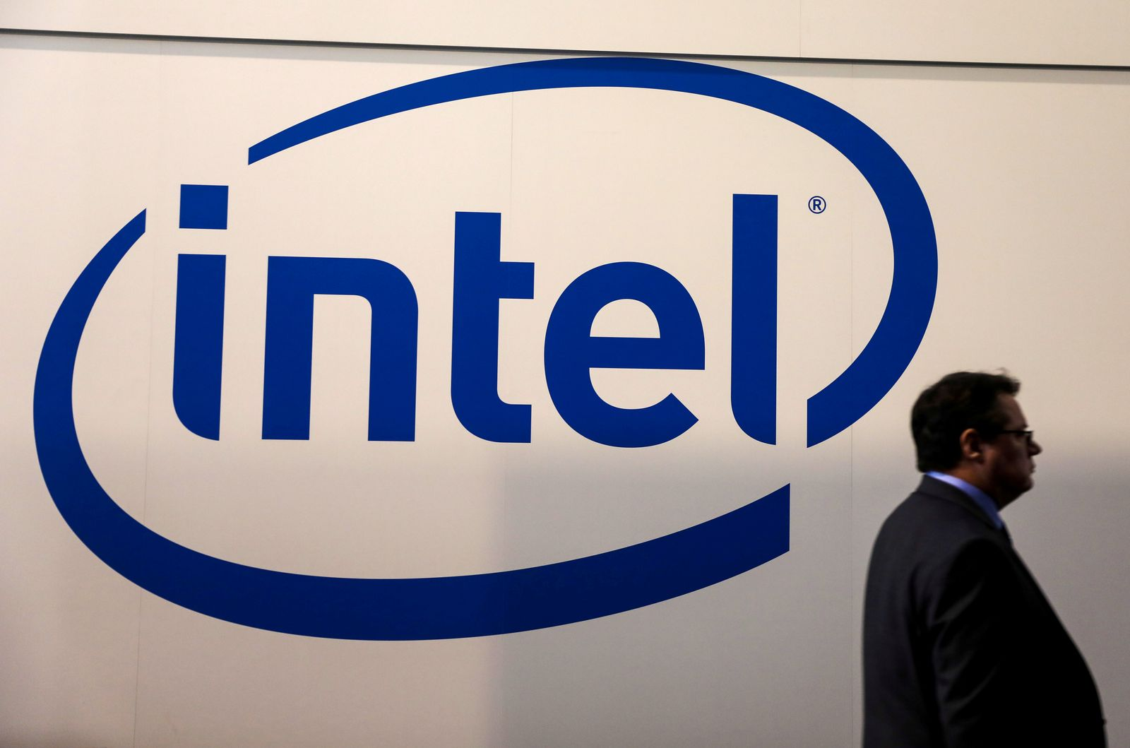 FILE PHOTO: FILE PHOTO: A visitor passes an Intel logo at the Mobile World Congress in Barcelona