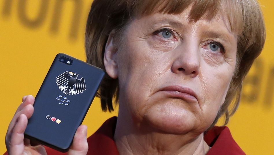 German Chancellor Angela Merkel holds a BlackBerry Z10 smart phone: Will the company face a setback following claims the NSA can spy on its phones?