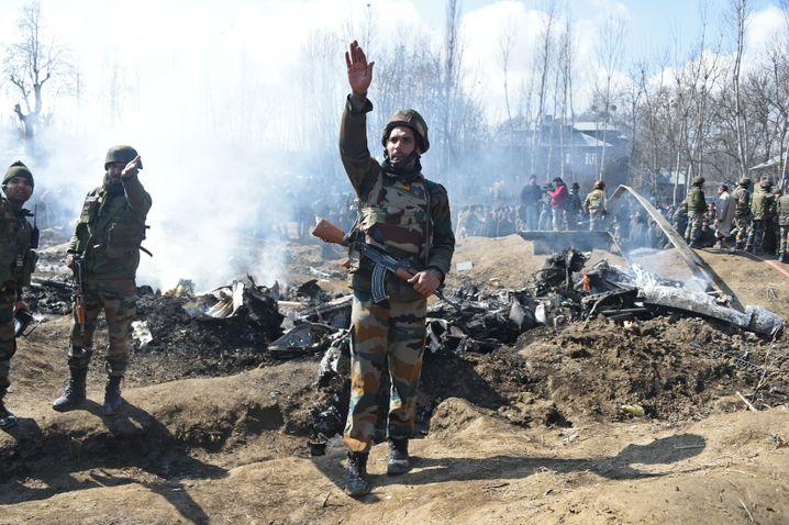 Indische Soldaten neben brennenden Wrackteilen im Bezirk Bugdam