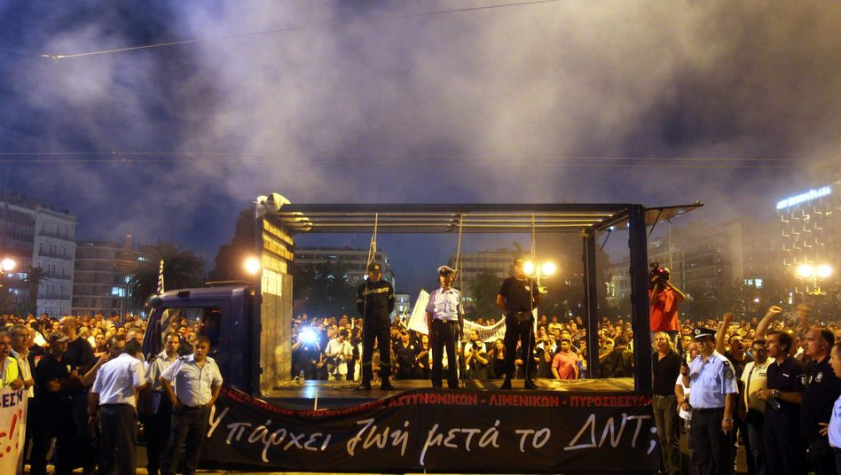 Officers from Greece's police, fire brigade and coast guard stage a symbolic hanging in front of the Greek Parliament in Athens on Sept. 6. to protest against austerity policies.