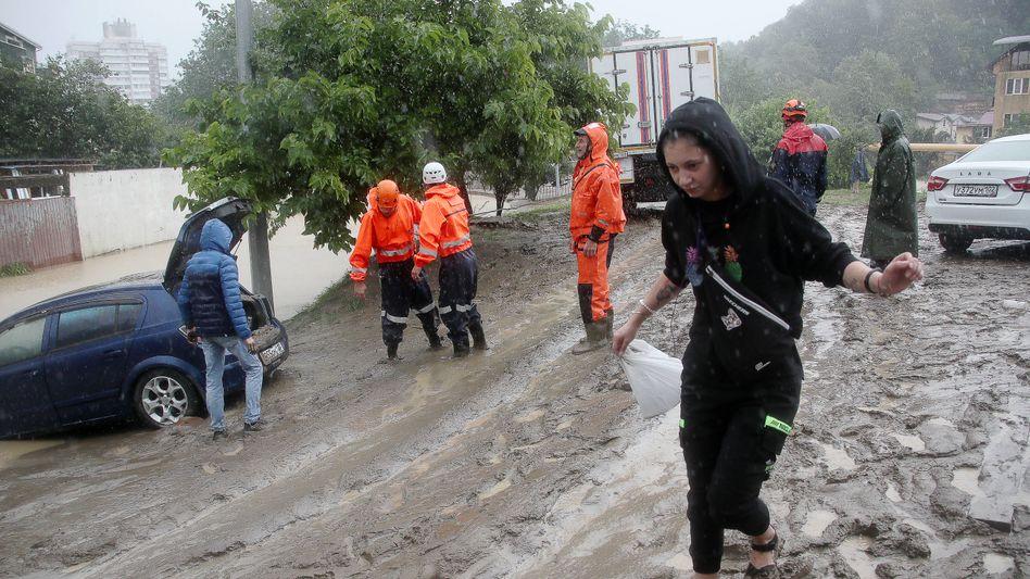 Einsatzkräfte helfen Anwohnerinnen und Anwohnern eines überschwemmten Viertels