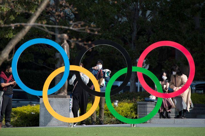 Menschen fotografieren die Olympischen Ringe vor dem Olympischen Museum in Tokio
