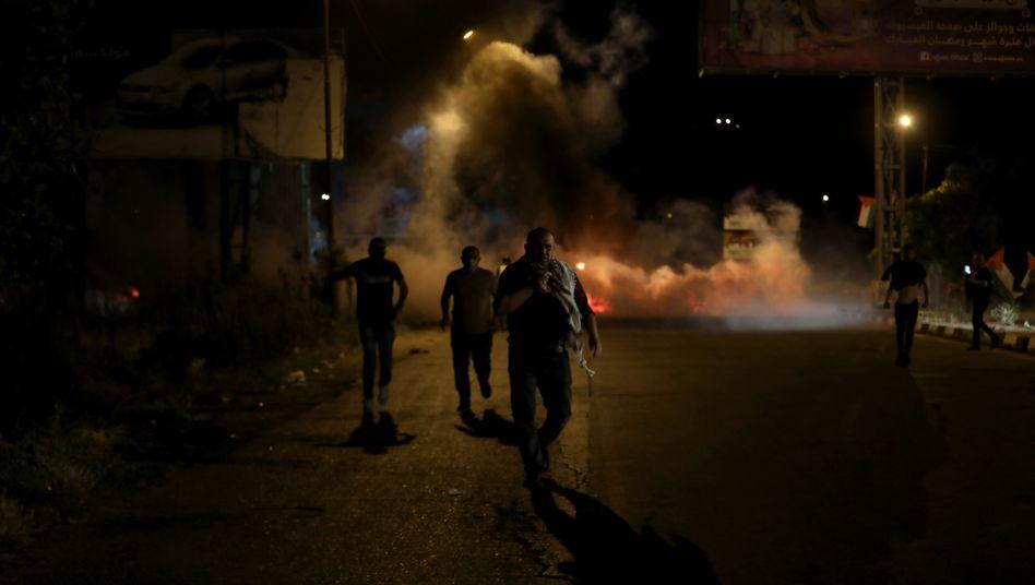 Palästinensische Demonstranten suchen Schutz vor Tränengas bei Zusammenstößen mit israelischen Truppen