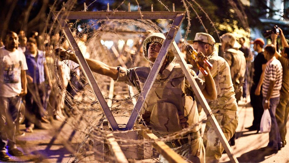 Egyptian soldiers remove barbed wire surrounding the Supreme Constitutional Court in Cairo ahead of planned demonstrations on August 18, 2013.