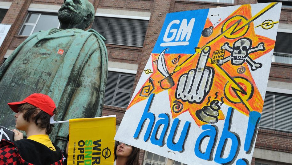 """Opel workers on Thursday protested the GM decision not to sell the German automaker after all. The sign reads: """"GM, Get Out of Here!"""""""