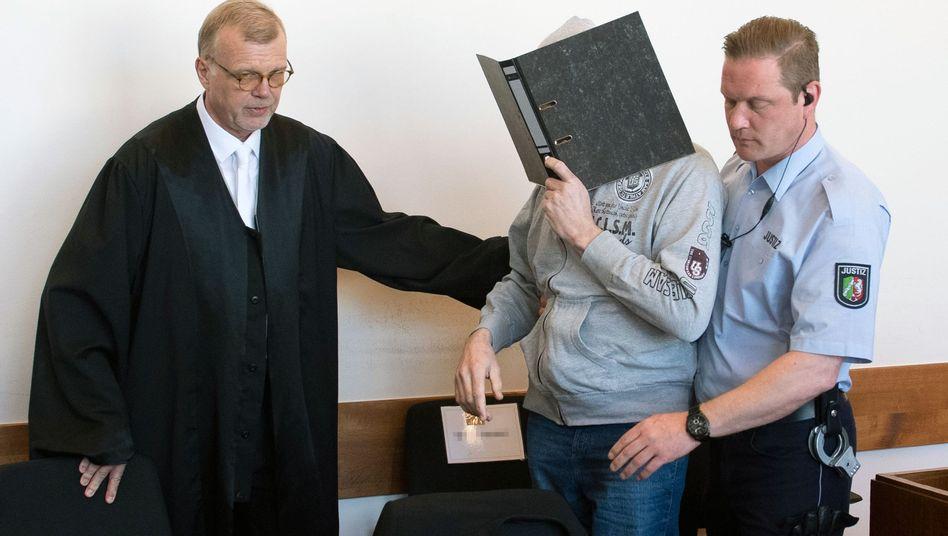 Prozessauftakt in Detmold: Der Angeklagte Andreas V. wird von einem Justizmitarbeiter in den Saal des Landgerichts geführt. Links im Bild sein Verteidiger Johannes Salmen.