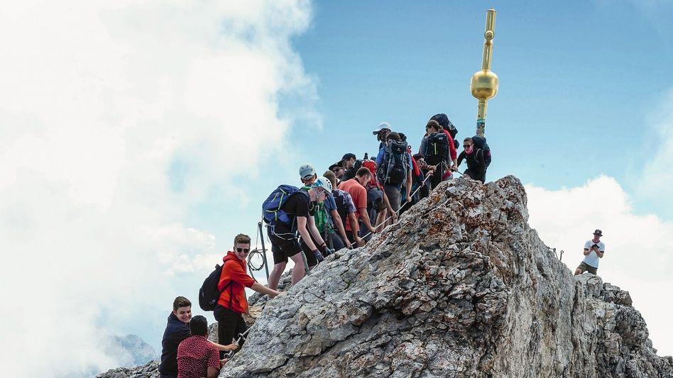 Touristen auf der Zugspitze: In Turnschuhen und T-Shirt zum Kreuz