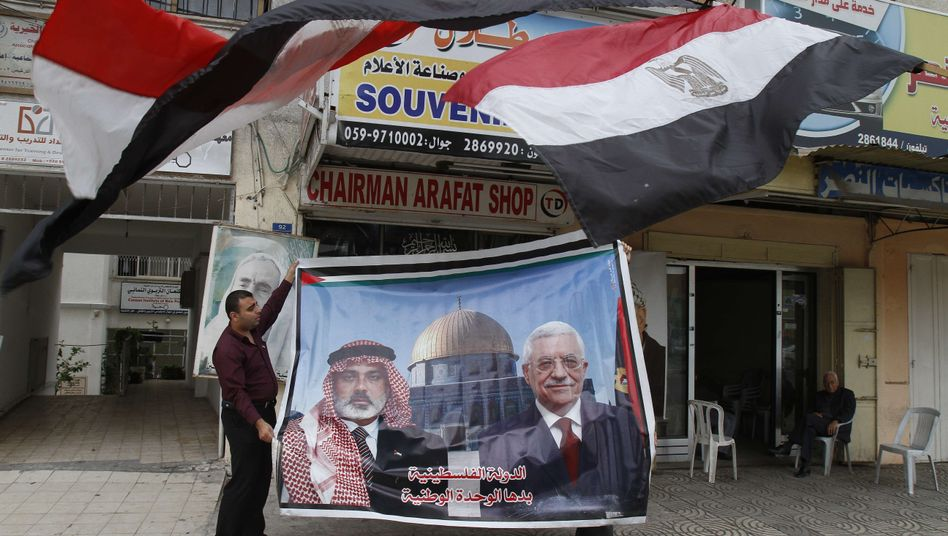A Palestinian vendor with a photo depicting Hamas leader in the Gaza Strip Ismail Haniya and Palestinian President Mahmoud Abbas.