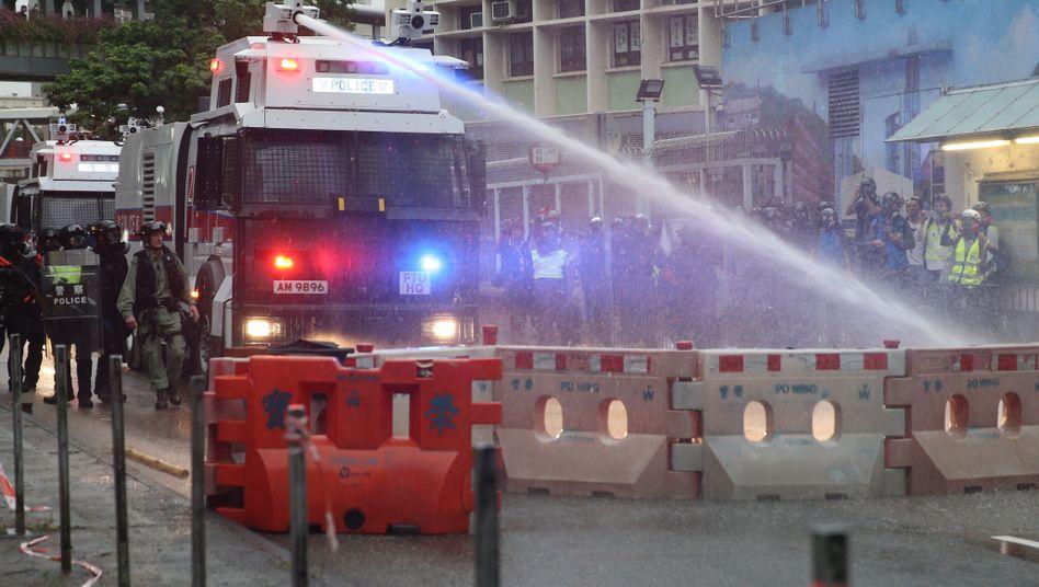 Ein Polizeieinsatzwagen mit Wasserkanone entfernt eine Straßenbarrikade der Demonstranten