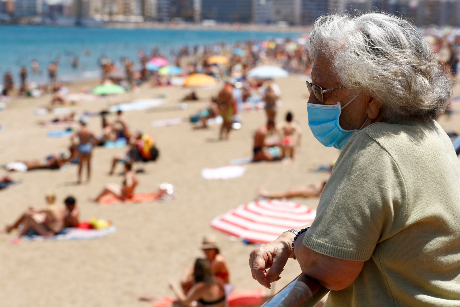 FILE PHOTO: A woman wearing a face mask watches people sunbathing on the Las Canteras beach