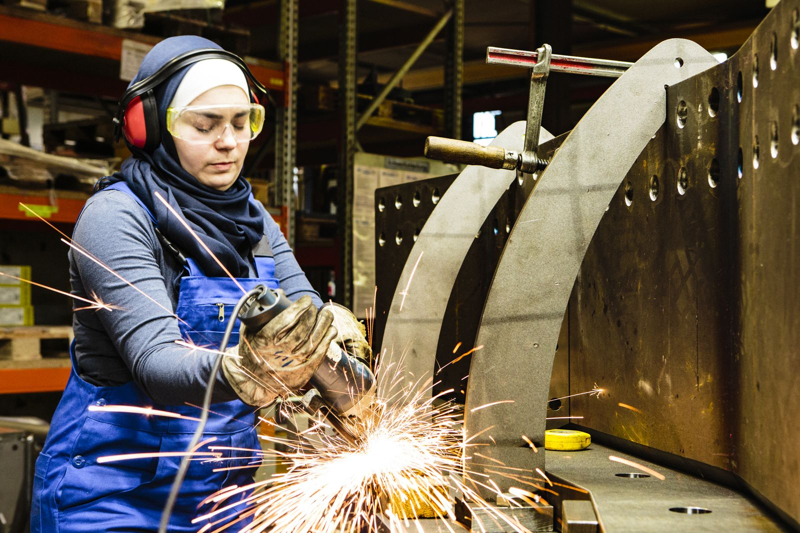 EINMALIGE VERWENDUNG Young female trainee works with a grinder in a workshop, flying sparks