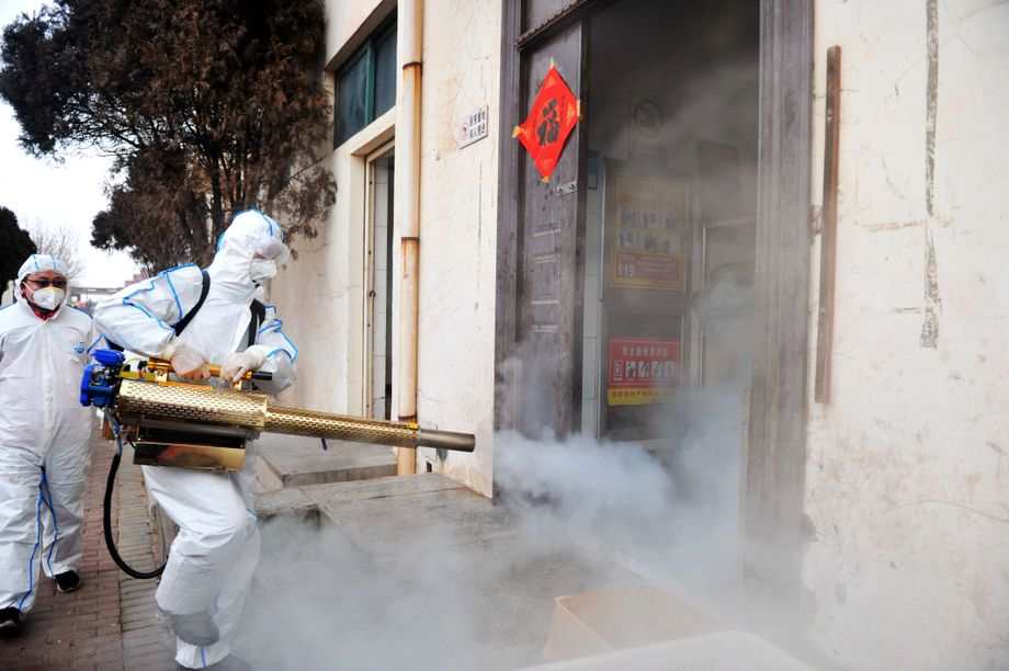 A volunteer in a protective suit disinfects a neighborhood in Qingdao in east China's Shangdong province.