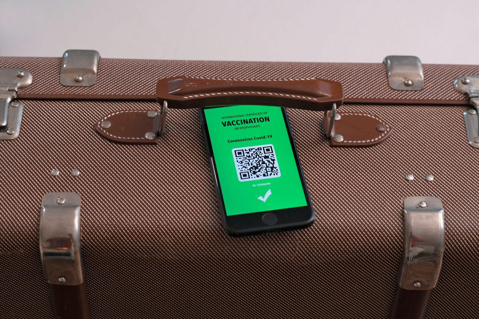 17.03.2021, Symbolbild, Impfung. Ein imagin?rer Impfpass in digitaler Form auf dem Smartphone iPhone auf einem Reisekoff