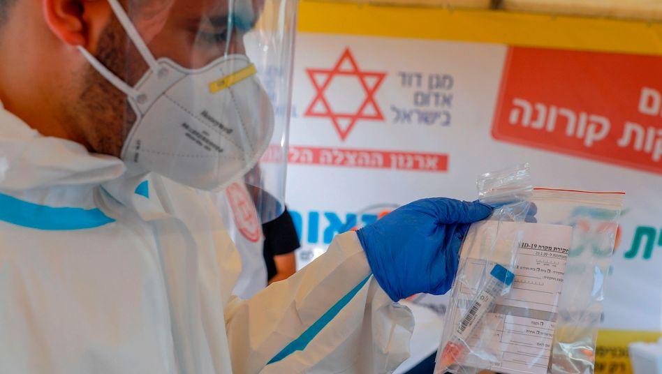 Ein israelischer Sanitäter hält einen Plastikbeutel mit einem Rachenabstrich