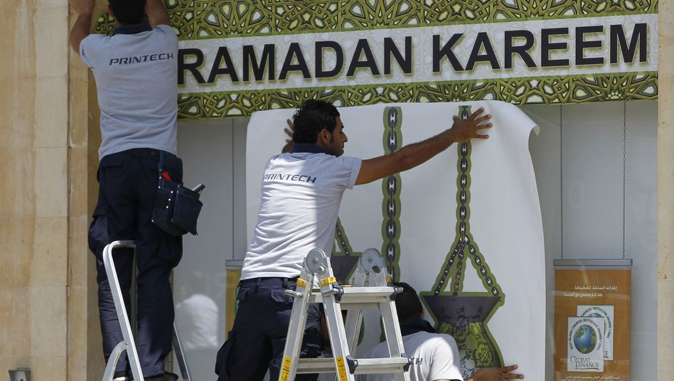 Lebanese workers hang a banner preparing for the holy month of Ramadan in a bank window in Beirut.