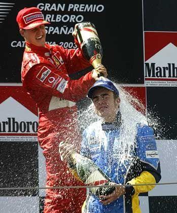 Klebrige Angelegenheit: Grand-Prix-Sieger Michael Schumacher gratuliert dem Spanier Fernando Alonso mit der obligatorischen Champagner-Dusche zu seinem Podiumsplatz