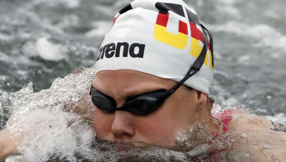 Bei starken Wellen und Regen schwimmt Finnia Wunram zur Silbermedaille