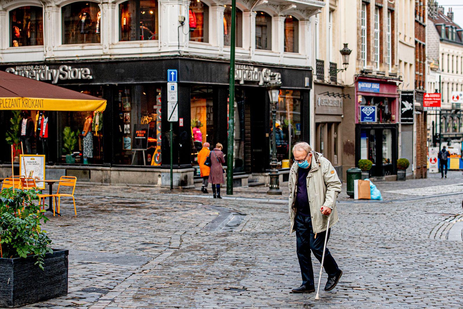 An elderly man wearing a facemask walks on the street. The