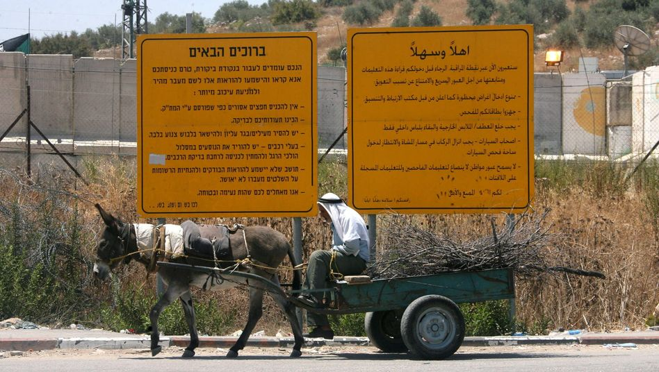 A Palestinian man rides his donkey cart in front of Israel's controversial security fence.