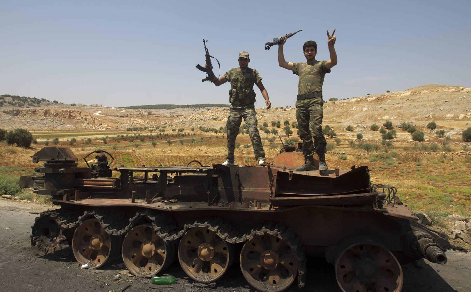 Syrien Rebellen auf ausgebranntem Panzer